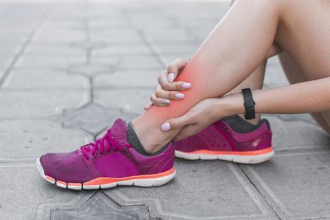 female athlete having ankle injury sitting pavement 23 2147888984 large